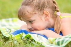 La muchacha de cinco años miente en prado verde y el tacto mirando la hierba Imagen de archivo libre de regalías