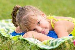 La muchacha de cinco años miente en un prado verde y el tacto de la mirada al marco Foto de archivo