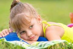 La muchacha de cinco años miente en una cama en prado verde y mira cuidadosamente a un lado Fotografía de archivo