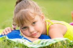 La muchacha de cinco años miente en una cama en un prado verde y el tacto de la mirada al marco Imagen de archivo