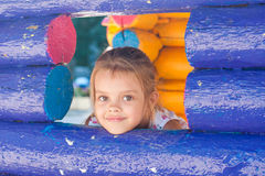 La muchacha de cinco años mira hacia fuera de una ventana de madera Fotos de archivo libres de regalías