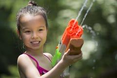 La muchacha de cinco años que juega con arroja a chorros el juguete fotos de archivo
