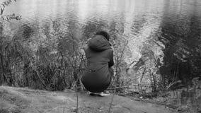 La muchacha de congelación tiembla de un frío, sentándose en el banco del río Tristeza, drama Vídeo monocromático almacen de video