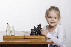 La muchacha de cuatro años aprende jugar a ajedrez Imagen de archivo