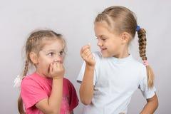 La muchacha de cuatro años con horror mira el diente perdido en su mano una muchacha de seis años Imagen de archivo