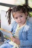 La muchacha de cuatro años con las coletas en una chaqueta azul está sentando ingenio Imagen de archivo libre de regalías