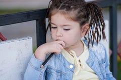 La muchacha de cuatro años con las coletas en una chaqueta azul pensaba Foto de archivo libre de regalías