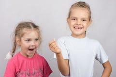 La muchacha de cuatro años con sorpresa mira fijamente el diente perdido en su mano una muchacha de seis años Foto de archivo