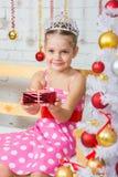 La muchacha de cuatro años estira adelante un pequeño regalo que sienta los árboles de navidad nevosos Imagen de archivo libre de regalías