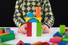 La muchacha de cuatro años juega en el diseñador en la tabla Juguetes de madera, diseñador colorido del ` s de los niños, fondo n Fotos de archivo libres de regalías