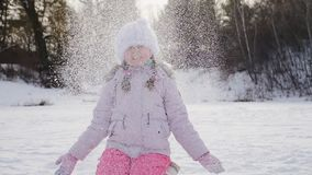 La muchacha de diez años alegre lanza nieve para arriba metrajes