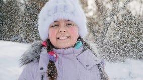 La muchacha de diez años alegre lanza nieve para arriba almacen de metraje de vídeo
