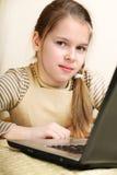 La muchacha de diez años trabaja en una computadora portátil, Imagenes de archivo