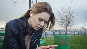 La muchacha de Dissapointed con el pelo rubio largo en la chaqueta de cuero endereza el artilugio del uso que se sienta en el ban Imagenes de archivo