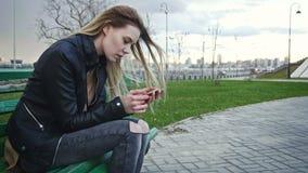 La muchacha de Dissapointed con el pelo rubio largo en la chaqueta de cuero endereza el artilugio del uso que se sienta en el ban Fotos de archivo libres de regalías