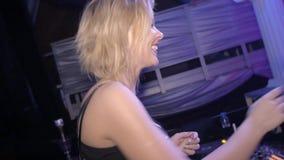 La muchacha de DJ en danza del top de los cristales, canta en micrófono en la placa giratoria en club nocturno almacen de metraje de vídeo
