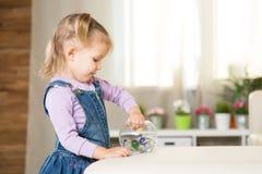 La muchacha de dos años de edad juega en el cuarto Imagenes de archivo