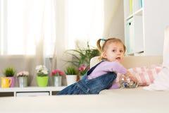 La muchacha de dos años de edad juega en el cuarto Fotografía de archivo