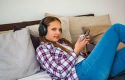 La muchacha de Eenager se divierte con la colocación móvil en la cama que escucha la música de un smartphone Foto de archivo