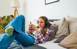 La muchacha de Eenager se divierte con la colocación móvil en la cama que escucha la música de un smartphone Imágenes de archivo libres de regalías