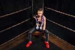 La muchacha de encajonamiento de la moda en rotura se sienta en una silla que descansa en un anillo de la competencia de boxeo Foto de archivo