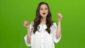 La muchacha de envía besos a otros, agita su mano Pantalla verde almacen de video