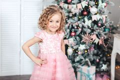 La muchacha de Ittle en un vestido rosado solemne se está colocando cerca del árbol de navidad Fotografía de archivo libre de regalías