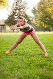 La muchacha de la aptitud que hace ejercicios apoya en el parque Foto de archivo