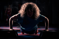 La muchacha de la aptitud se está resolviendo con de pasos Morenita fuerte con el pelo rizado que hace aeróbicos en de pasos Chic Imágenes de archivo libres de regalías