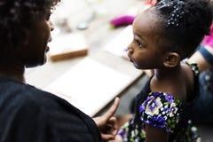 La muchacha de la ascendencia africana está escuchando su profesor imagen de archivo libre de regalías