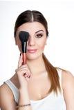 La muchacha de la belleza compone al artista con el cepillo del maquillaje El día de fiesta brillante compensa a la mujer morena  imágenes de archivo libres de regalías