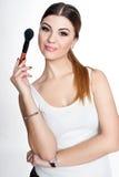 La muchacha de la belleza compone al artista con el cepillo del maquillaje El día de fiesta brillante compensa a la mujer morena  imagen de archivo
