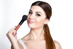La muchacha de la belleza compone al artista con el cepillo del maquillaje El día de fiesta brillante compensa a la mujer morena  foto de archivo