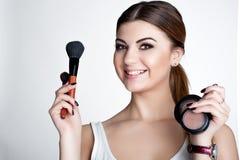 La muchacha de la belleza compone al artista con el cepillo del maquillaje El día de fiesta brillante compensa a la mujer morena  foto de archivo libre de regalías