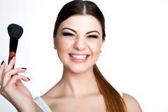 La muchacha de la belleza compone al artista con el cepillo del maquillaje El día de fiesta brillante compensa a la mujer morena  imagenes de archivo
