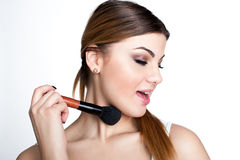 La muchacha de la belleza compone al artista con el cepillo del maquillaje El día de fiesta brillante compensa a la mujer morena  fotos de archivo