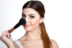 La muchacha de la belleza compone al artista con el cepillo del maquillaje El día de fiesta brillante compensa a la mujer morena  imagen de archivo libre de regalías