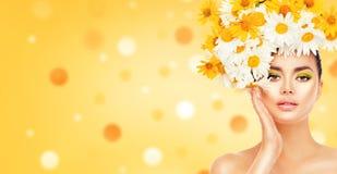 La muchacha de la belleza con la margarita florece el peinado que toca su piel Foto de archivo libre de regalías