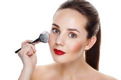 La muchacha de la belleza con maquillaje del final de cepillo aplica el highlighter M brillante Foto de archivo libre de regalías