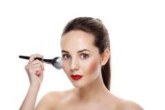 La muchacha de la belleza con maquillaje del final de cepillo aplica el highlighter M brillante Fotos de archivo libres de regalías