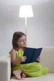La muchacha de la belleza leyó el libro en el sofá fotos de archivo libres de regalías