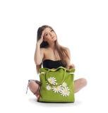 La muchacha de la belleza se sienta con el bolso verde de la playa Foto de archivo