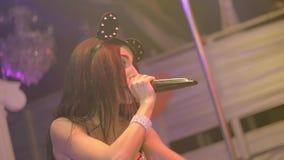 La muchacha de la bujía métrica en oídos de ratón, canta, aumenta las manos en la etapa del club nocturno Cámara lenta almacen de video