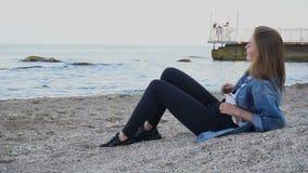 La muchacha de la cámara lenta disfruta de día de fiesta en ciudad del mar y a medias dormido encantadores en la playa contra el  almacen de metraje de vídeo
