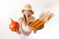 La muchacha de la cosecha con el sombrero está ofreciendo la calabaza y el maíz Foto de archivo libre de regalías