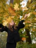 La muchacha de la diversión sacude follaje de caída Fotos de archivo