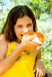 La muchacha de la diversión come el perrito caliente Fotografía de archivo libre de regalías