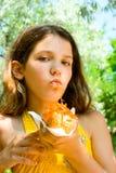 La muchacha de la diversión come el perrito caliente en la naturaleza Foto de archivo