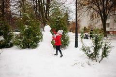 La muchacha de la edad de escuela construye un muñeco de nieve Fotografía de archivo libre de regalías