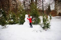 La muchacha de la edad de escuela construye un muñeco de nieve Imagenes de archivo